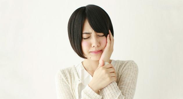 歯科口腔外科・頬を押さえる女性